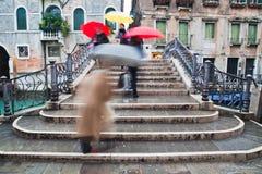 Leute mit den Regenschirmen, die eine Brücke kreuzen Stockbild