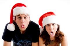 Leute mit der Weihnachtshut und -herstellung der sonderbaren Gesichter Stockfoto