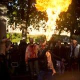 Leute mit Feuer, wie ein Zombie auf eine Straße während eines Zombiewegs in Paris vorführt Stockbilder