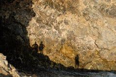 Leute mit Fotografen als Schatten auf einer Felsenwand stockfotos