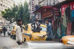 Leute mit gelber Weinlese fahren auf die Straße in Kolkata, Indien mit einem Taxi Lizenzfreies Stockfoto