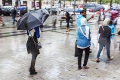 Leute mit Regenregenschirmen in der regnerischen Stadt Lizenzfreies Stockbild