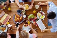 Leute mit Smartphones Lebensmittel bei Tisch essend Lizenzfreie Stockfotografie
