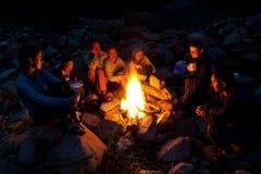 Leute nähern sich Lagerfeuer im Wald Lizenzfreies Stockfoto