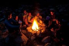 Leute nähern sich Lagerfeuer im Wald. Lizenzfreies Stockfoto