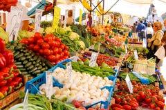 Leute nahe einem Zähler mit Gemüse auf einem Markt in Venedig, Ita Stockfotos