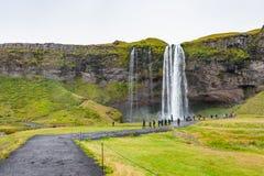 Leute nahe Seljalandsfoss-Wasserfall im Herbst Lizenzfreies Stockfoto