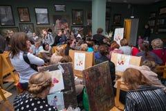 Leute nehmen an freier Werkstatt während des Tages der offenen Tür in der Aquarellschule teil Stockfotografie