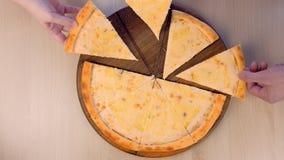 Leute nehmen Scheiben von Pizza Margarita mit verschiedenen Arten des Käses auf Draufsicht der Nahaufnahme des hölzernen Brettes stock video