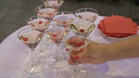 Leute nehmen von der Tabelle ein Glas Martini und Whisky Champagne in den Gläsern mit frischer Kirsche auf Tabelle und Partei Stockbild