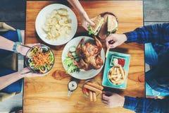 Leute-Partei und das Essen des gegrillten Huhns sind glückliches Genießen in ho lizenzfreie stockbilder