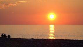 Leute passen den Sonnenuntergang in Georgia durch das Meer auf stock video