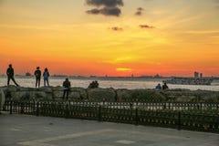 Leute passen Landschaft von Kadikoy, Istanbul bei Sonnenuntergang auf lizenzfreies stockbild