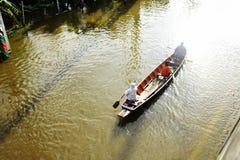 Leute reisen mit dem Boot auf der Straße während der Flut Lizenzfreie Stockfotografie