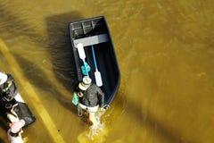 Leute reisen mit dem Boot auf der Straße während der Flut Stockfotos