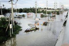 Leute reisen mit dem Boot auf der Straße während der Flut Lizenzfreie Stockbilder