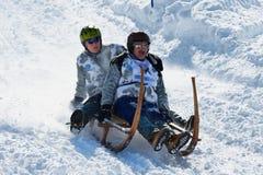 Leute reiten traditionellen Hornschlitten am 12. jährlichen Horn-Schlitten-Rennen von Alpiglen zu Grund in Grindelwald, die Schwe stockbilder