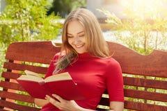 Leute, Rest, Hobby, Ferienkonzept Nette blonde Frau in der roten Strickjacke, die ihre lesenden lustigen Geschichten des Liebling Lizenzfreie Stockfotos