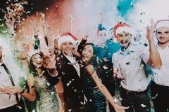 Leute in Santa Claus Cap Celebrating New Year lizenzfreie stockfotografie