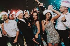 Leute in Santa Claus Cap Celebrating New Year stockfoto