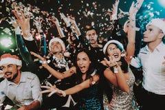 Leute in Santa Claus Cap Celebrating New Year lizenzfreie stockbilder