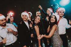 Leute in Santa Claus Cap Celebrating New Year lizenzfreies stockbild