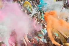 Leute schaffen Explosion von Farben mit farbigen Maisstärke-Paketen Stockfotos