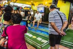 Leute sehen den touristischen Mann, Fischbadekurort am Nachtmarkt in Chiang Mai, Thailand zu tun lizenzfreie stockfotografie