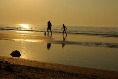 Leute silhouettieren auf dem Strand Lizenzfreies Stockfoto