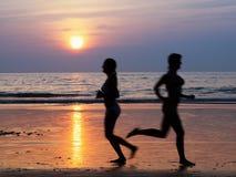 Leute silhouettieren Betrieb durch den Ozean am Sonnenuntergang Lizenzfreies Stockbild