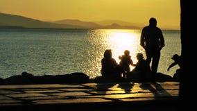 Leute silhouettieren nahe der Küste im Sonnenuntergang stock video footage