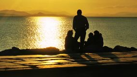 Leute silhouettieren nahe der Küste im Sonnenuntergang stock footage