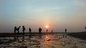Leute silhouettieren während des Sonnenaufgangs Stockbilder