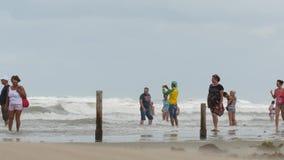 Leute sind gegen den Sturmwind Ein starker Wind brennt vom Meer durch Der Sturmwind steigt Hurrikan auf dem Meer stock footage