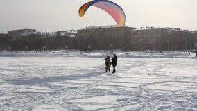Leute sind Gleitschirmfliegen auf dem See. stock footage