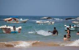 Leute sind, spritzend schwimmend und zwischen Fischerbooten Stockbild