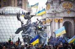 Leute sitzen auf dem Monument, das mit Flaggen während der Revolution in der Ukraine verziert wird Stockfotos