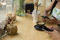 Leute sitzen auf dem Telefon und dem trinkenden Kaffee auf einem Holztisch in einem Restaurant Stockbilder