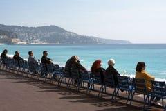 Leute sitzen auf den berühmten blauen Stühlen auf Promenade des Anglais, passen das azurblaue Meer auf und genießen den warmen So stockfoto