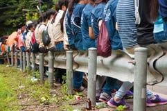 Leute sitzen auf Straßenrand Stockfoto