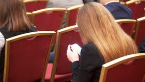 Leute sitzen in der großen Halle auf roten Stühlen bei der Geschäftskonferenz, Frauen mit Smartphone in den Händen stock video