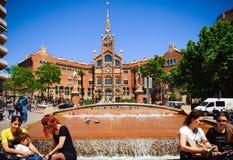 Leute sitzen nahe kleinem Brunnen nahe Gebäude von Old Hospital de Sant Paul in Barcelona, Spanien Stockfotos