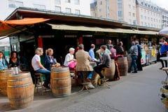 Leute sitzen um die Fässer und trinken Wein nahe der kleinen Weinhandlung Lizenzfreies Stockfoto
