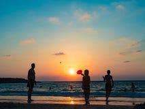 Leute spielen auf der Küste im Sommer in den Strahlen des Sonnenuntergangs Stockfoto