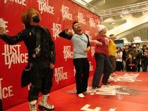 Leute spielen gerade Tanz für das Wii auf Stufe Stockfotos