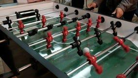Leute spielen Tabellenfußball Rote und schwarze Stücke foosball Spieler spinnen und schlagen den Ball Hände verdrehen Hebel, um z stock video