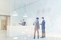 Leute sprechen in einer Halle nahe Aufnahmezähler mit Uhren Lizenzfreie Stockbilder