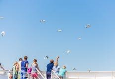 Leute stehen auf der Fähre und passen den Hintergrund des blauen Himmels der Seemöwen auf stockfoto