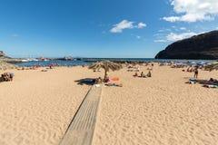 Leute stehen an einem sonnigen Tag am Strand in Machico still Madeira-Insel Stockbild