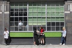 Leute stehen am Haus mit großen Fenstern im Stil 70 x Stockfoto